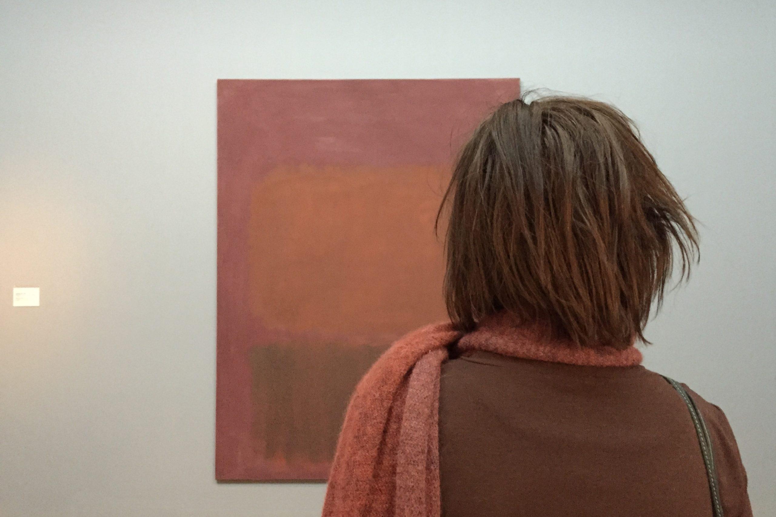 Eine Museumsbesucherin betrachtet ein Bild von Mark Rothko